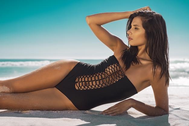 砂の上に横たわる美容女性