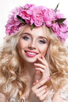 白い背景の上の美女。明るいウェーブのかかった髪とピンクの牡丹の花輪