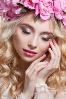 흰색 바탕에 아름다움 여자입니다. 밝은 물결 모양의 머리카락과 분홍색 모란의 화환