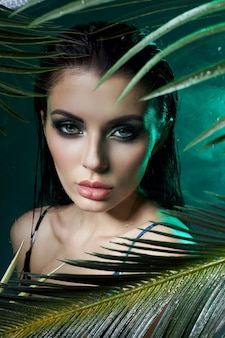 Beauty woman in palm leaves wet makeup, tropical portrait girl in green swimsuit in branches palm tree in studio, smoke and raindrops on glass. sexy woman with bright green makeup