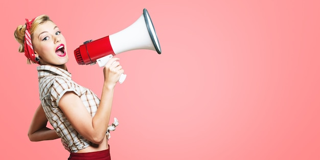 Beauty woman in pin-up style holding white-red megaphone and shouts