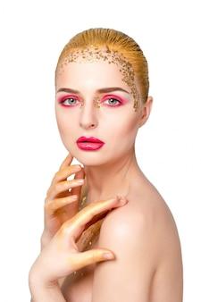 Красота женский портрет. красивая модельная девушка с идеальной свежей чистой кожей и ярким золотистым профессиональным макияжем. блондинка на белой стене с вечерним розово-золотым макияжем