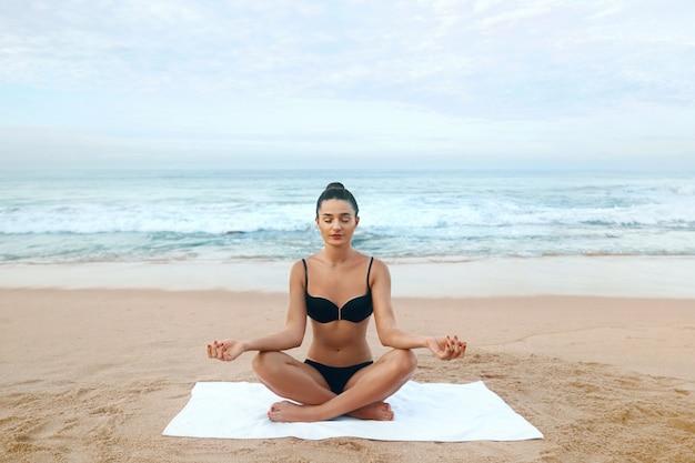 미인은 요가를 하고 해변에서 연꽃 자세로 명상을 합니다. 심사 숙고. 활동적인 라이프 스타일. 건강하고 요가 개념입니다. 피트니스 및 스포츠
