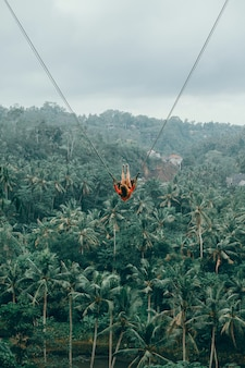 Beauty woman on swing, bali nature, happy face, jungle