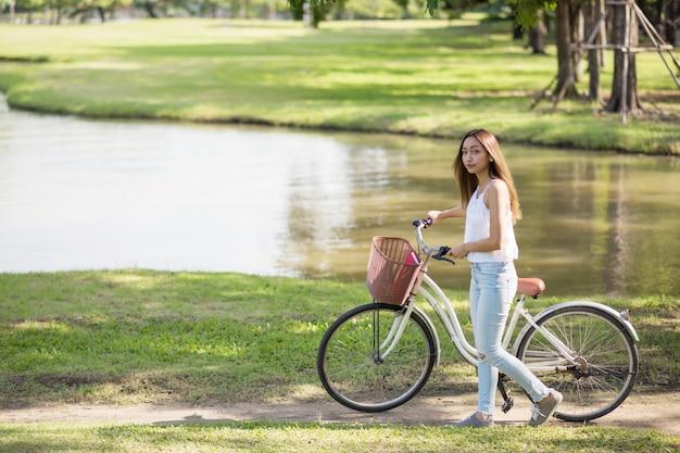 Beauty woman walk wheel bike in urban park pond