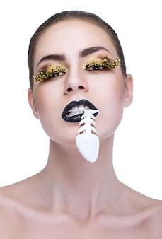Красота женщины с черными губами и рыбой во рту на белом фоне