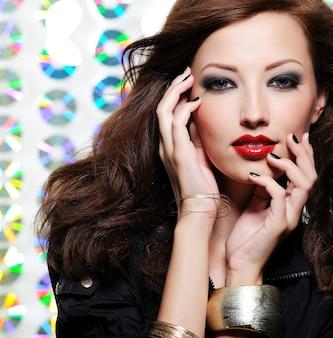 Donna di bellezza con trucco occhi moda brillante e labbra rosse