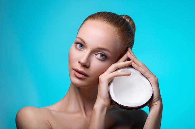Женщина красоты с кокосом в руках. забота о коже.
