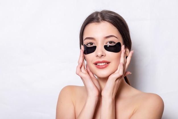 Женщина красоты с повязками на глазу. женщина с естественным макияжем и черными пятнами коллагена на свежей коже лица. лечение кожи вокруг глаз