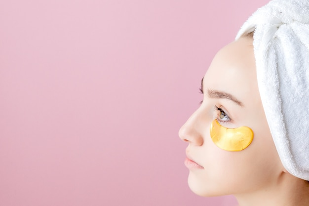 Beauty woman with eye patches on pink background