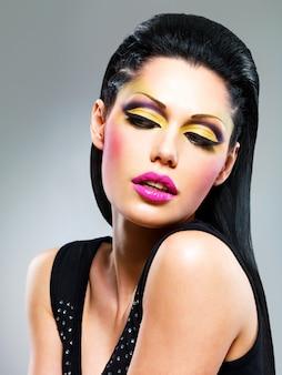 Красота женщины с модным макияжем на лице позирует