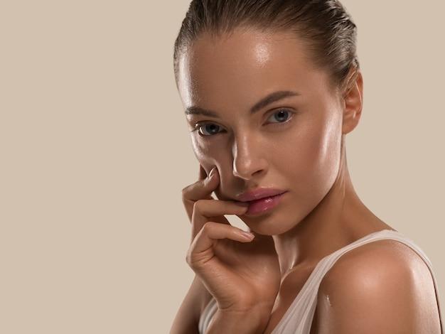 손으로 건강한 자연을 가진 미인 여성 깨끗하고 신선한 피부 개념 색상 배경 갈색