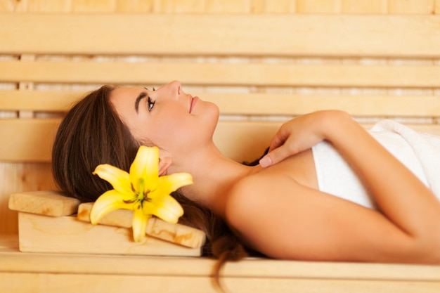 Beauty woman with lily in hair relaxing in sauna