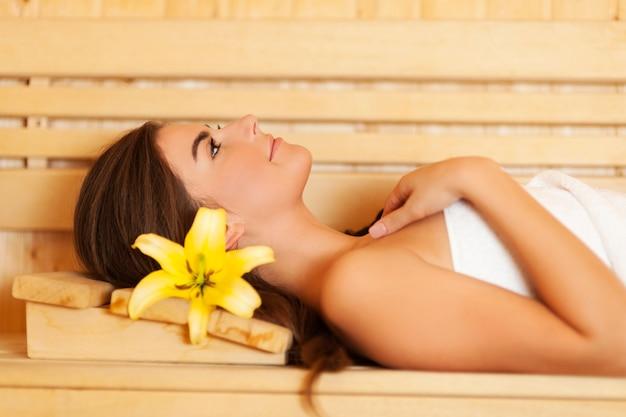 Женщина красоты с лилией в волосах, расслабляясь в сауне