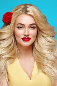 긴 곱슬 금발 머리 꽃 머리 손질 된 손톱 유행 색상 파란색과 노란색을 가진 미인