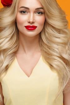 긴 곱슬 금발 머리 꽃 머리 손질 된 손톱 유행 색상 오렌지와 노란색을 가진 미인