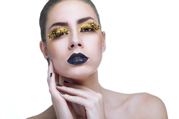 Красота женщины с длинными желтыми ресницами и черными губами на белом фоне