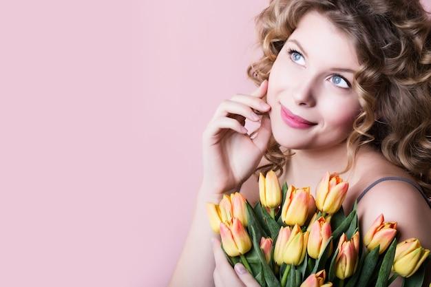 Женщина красоты с букетом цветов весны на пинке.