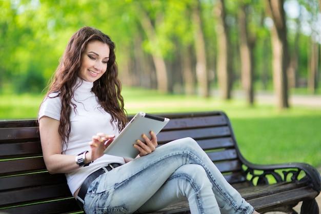 Красота женщины с планшетом на скамейке в зеленом парке