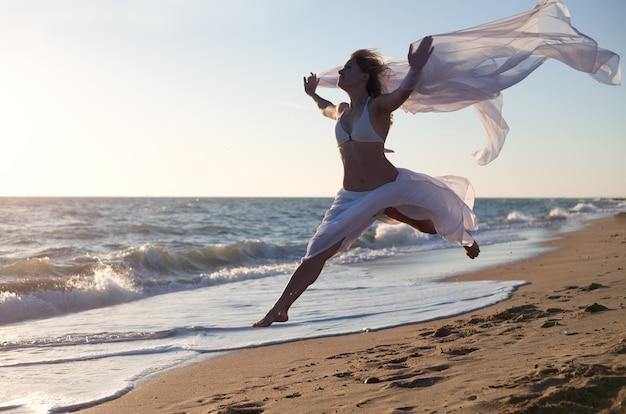 바다 해변에서 흰 드레스와 아름다움 여자