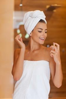 Donna di bellezza avvolta in un asciugamano che applica profumo