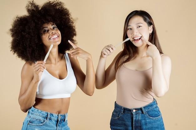 Красота женщин африканских и азиатских зубной щеткой, на бежевом фоне