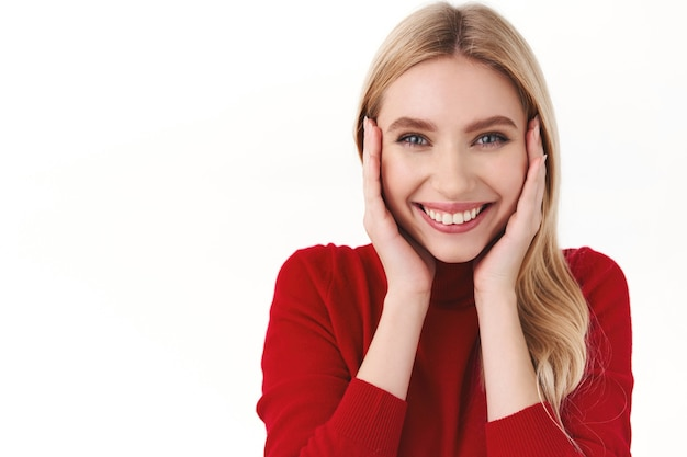 美容、女性、ファッションのコンセプト。ブロンドの長い髪、赤いタートルネックを持つ愛らしい女性の若い白人女性