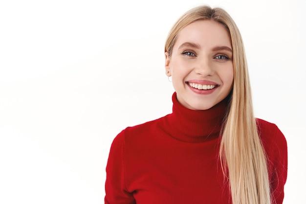 Bellezza, donne e concetto di moda. donna bionda attraente allegra con capelli lunghi, dolcevita rosso, sorridente con un sorriso sincero e compiaciuto