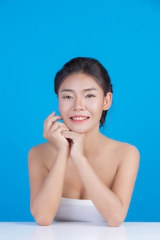 The beauty of women with perfect skin health images touching her face and smiling like a spa to pamper her skin blue