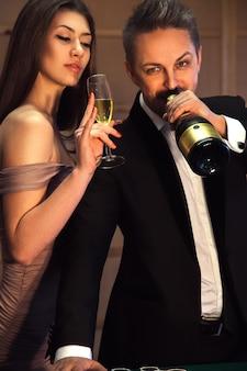 美しさの若い大人のカップルはシャンパンを飲み、何かを祝います。休日とお祝いの概念