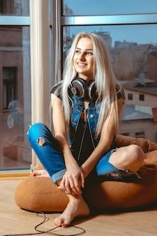 カジュアルなジーンズの服を着た美しさの若い大人の女性は、cauchでポーズをとって目をそらします。リラックス、リフレッシュ、レジャーの概念
