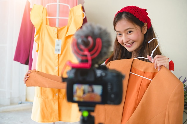 Beauty young asian vlogger blogger interview with professional dslr digital camera video.