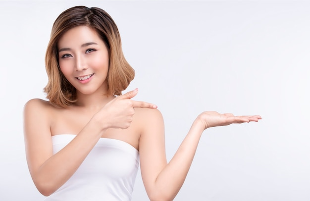 Beauty young asian woman pointing hand for product on white background