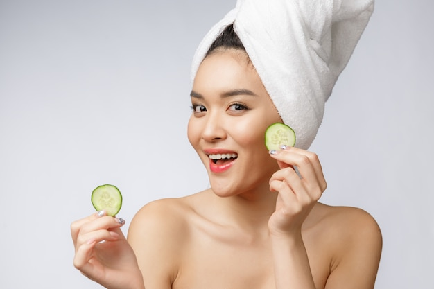 Beauty young asian women skin care image with cucumber on white background studio.