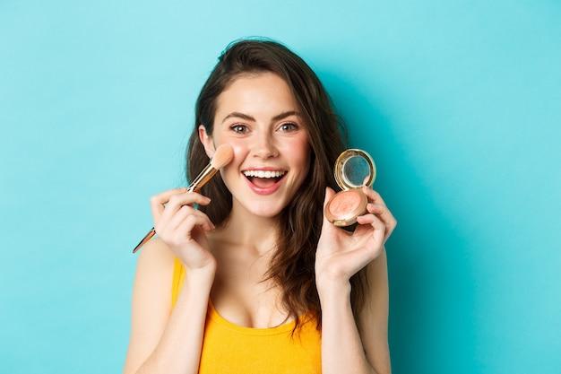 아름다움. 웃고, 브러시로 화장을 하고, 카메라에 얼굴을 붉히며, 파란색 배경 위에 서 있는 젊은 매력적인 여성. 복사 공간