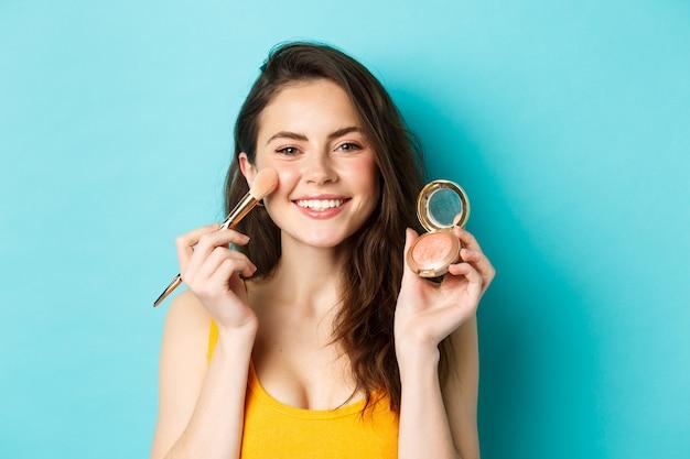 아름다움. 웃고, 브러시로 화장을 하고, 카메라에 얼굴을 붉히며, 파란색 배경 위에 서 있는 젊은 매력적인 여성