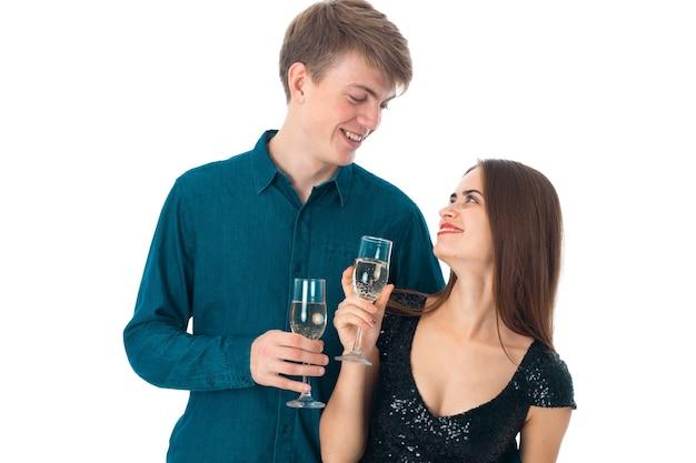 Молодая пара красоты в любви с двумя бокалами шампанского в студии на белом фоне