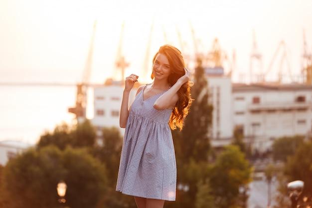 Красавица молодая рыжая девушка в платье позирует на закате
