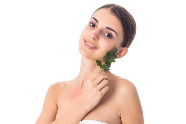 Красота маленькая девочка заботится о ее коже с зелеными листьями в руках, изолированных на белом фоне. концепция здравоохранения. концепция ухода за телом. молодая женщина со здоровой кожей.