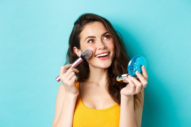 아름다움. 젊은 매력적인 소녀는 주머니 거울과 브러시로 화장을 하고 웃고 로고를 올려다보며 파란색 배경에 서 있습니다.