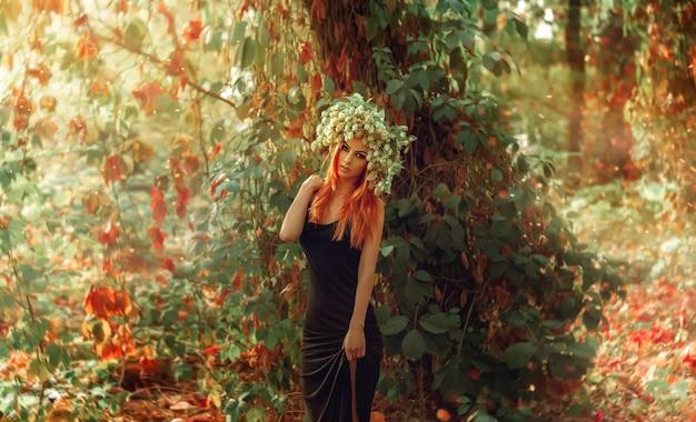 森の中で屋外の頭にホップでポーズをとる美の若い赤毛の女性