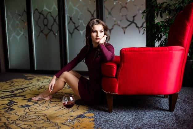 Красота молодая сексуальная женщина пьет красное вино над праздником мигает