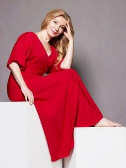 はためく赤いドレスの美しさの若い女性。