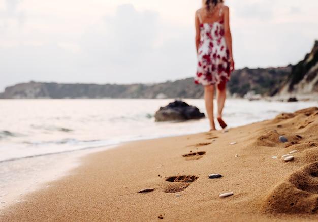 Красота молодой женщины в стильном платье, идущей босиком по пляжу, оставляя следы на песке на закате над горизонтом. концепция путешествий и отдыха.