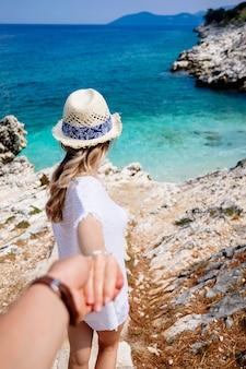 白い服、麦わら帽子、サングラスの美しさの若い女性が手で男を保持し、ビーチに歩いて