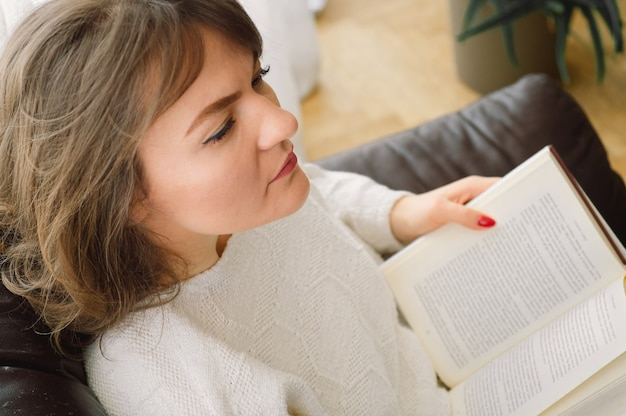 美しさ若い女性は家で本を読んでいます