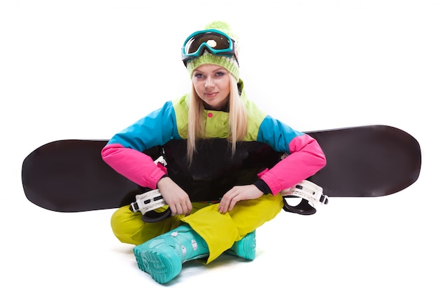 Beauty young woman in ski suit and ski glasses sit with sbowboard