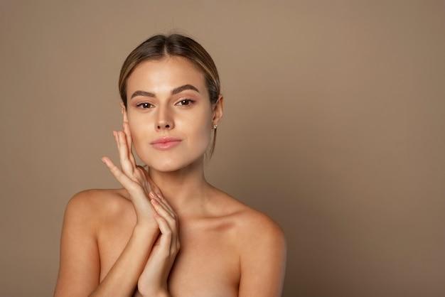 Молодая женщина красоты касается ее лица руками. молодая красивая дама с естественным макияжем