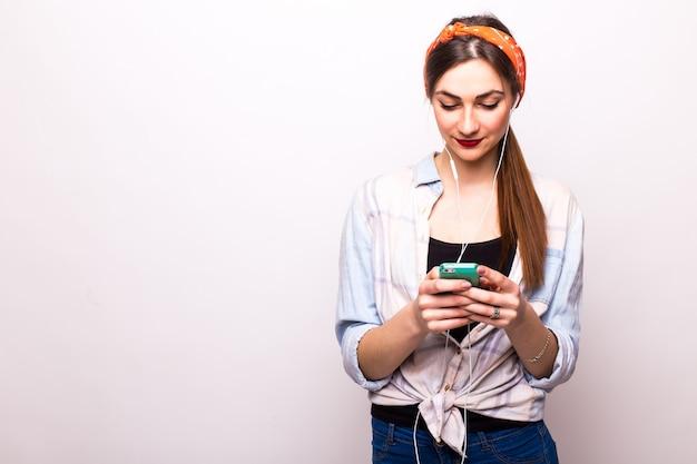 Красота молодой женщины с помощью и чтения смарт-телефона на белом