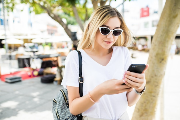 日当たりの良い夏の通りで屋外でスマートフォンを使用して美しい若い女性